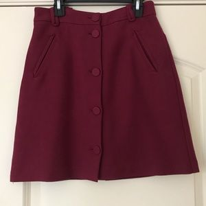 Burgundy/maroon mini skirt with buttons.